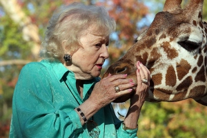 Betty White whispering to a giraffe